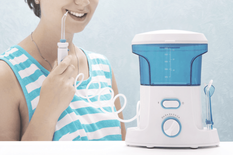 a girl using a water flosser